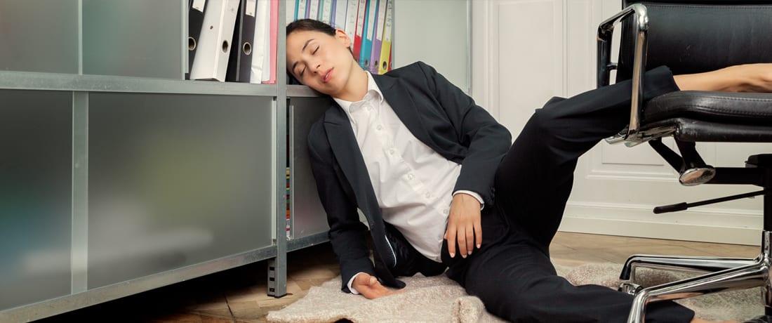 Junge Frau ist im Büro am Büchergestell eingeschlafen. Happy Matratzen kaufen