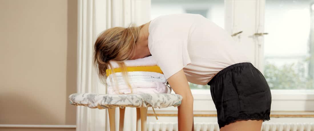 Junge Frau, die mit dem Kopf auf der Wäsche auf dem Bügelbrett eingeschlafen ist. Matratze bestellen bei happy.