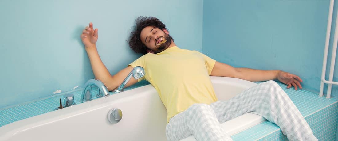 Giovane uomo che dorme per metà sdraiato sopra la vasca da bagno. Ordina ora il tuo materasso svizzero online da happy.ch.